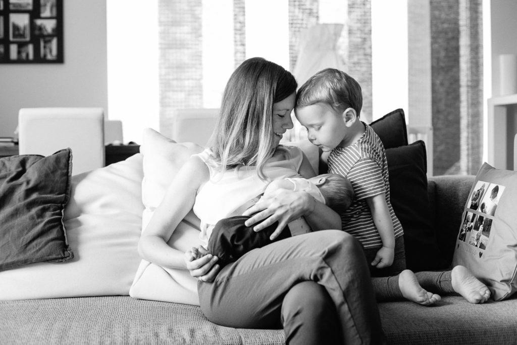 Mutter und Bruder schauen Neugeborenes verliebt an
