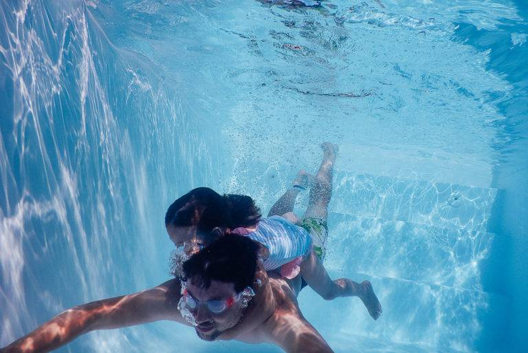 Vater und Tochter tauchen durchs Wasser