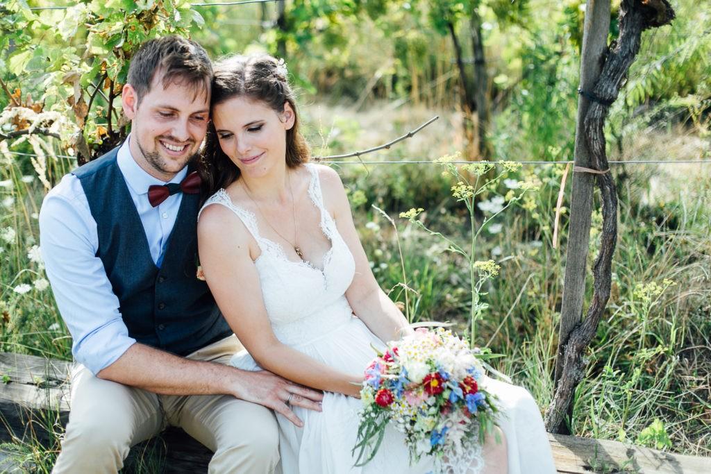 Brautpaar sitzt zwischen Weinstöcken
