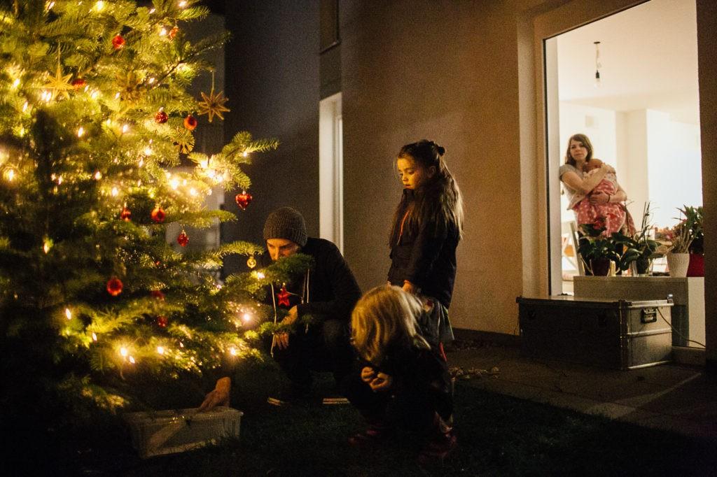 Familie steht unter dem Christbaum