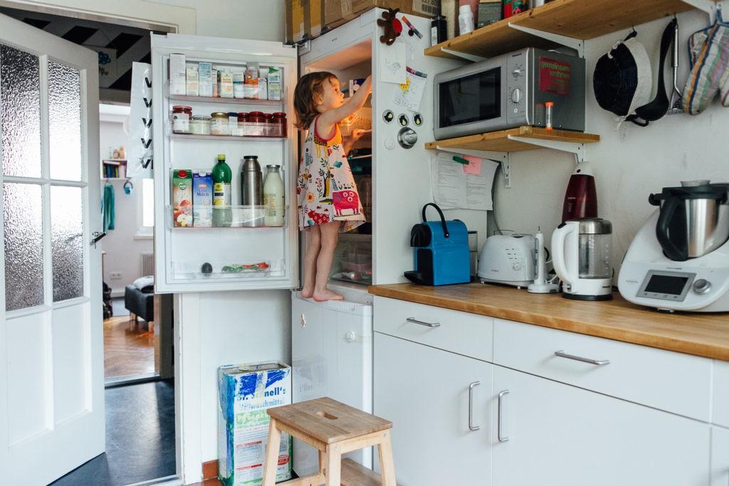 kleines Kind steht im Kühlschrank