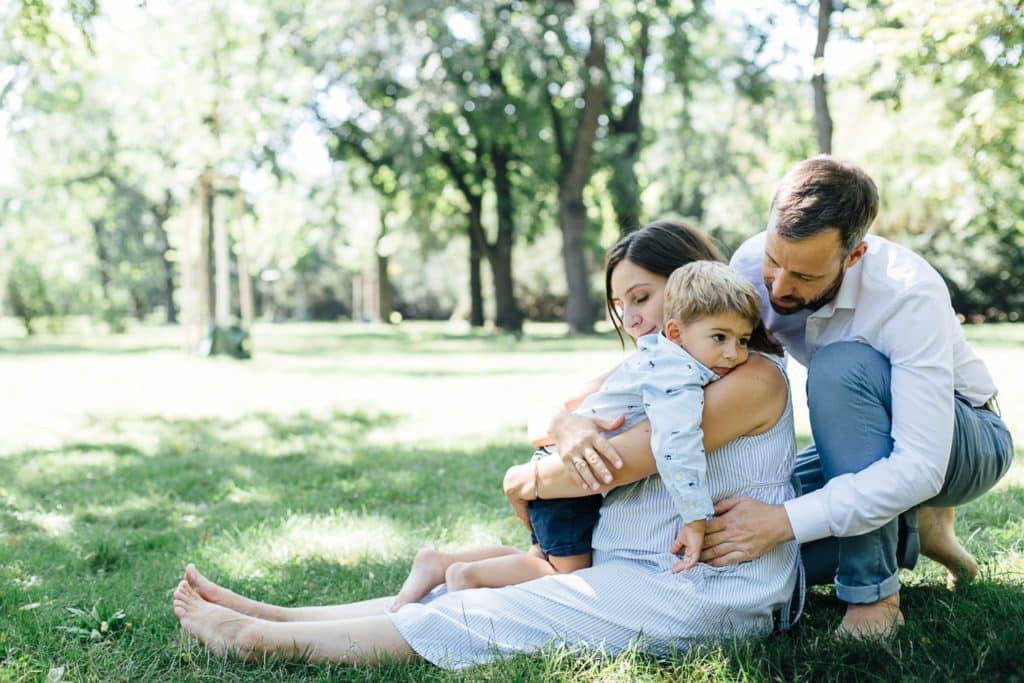 schwangere Mutter, Vater und Sohn kuscheln im Gras