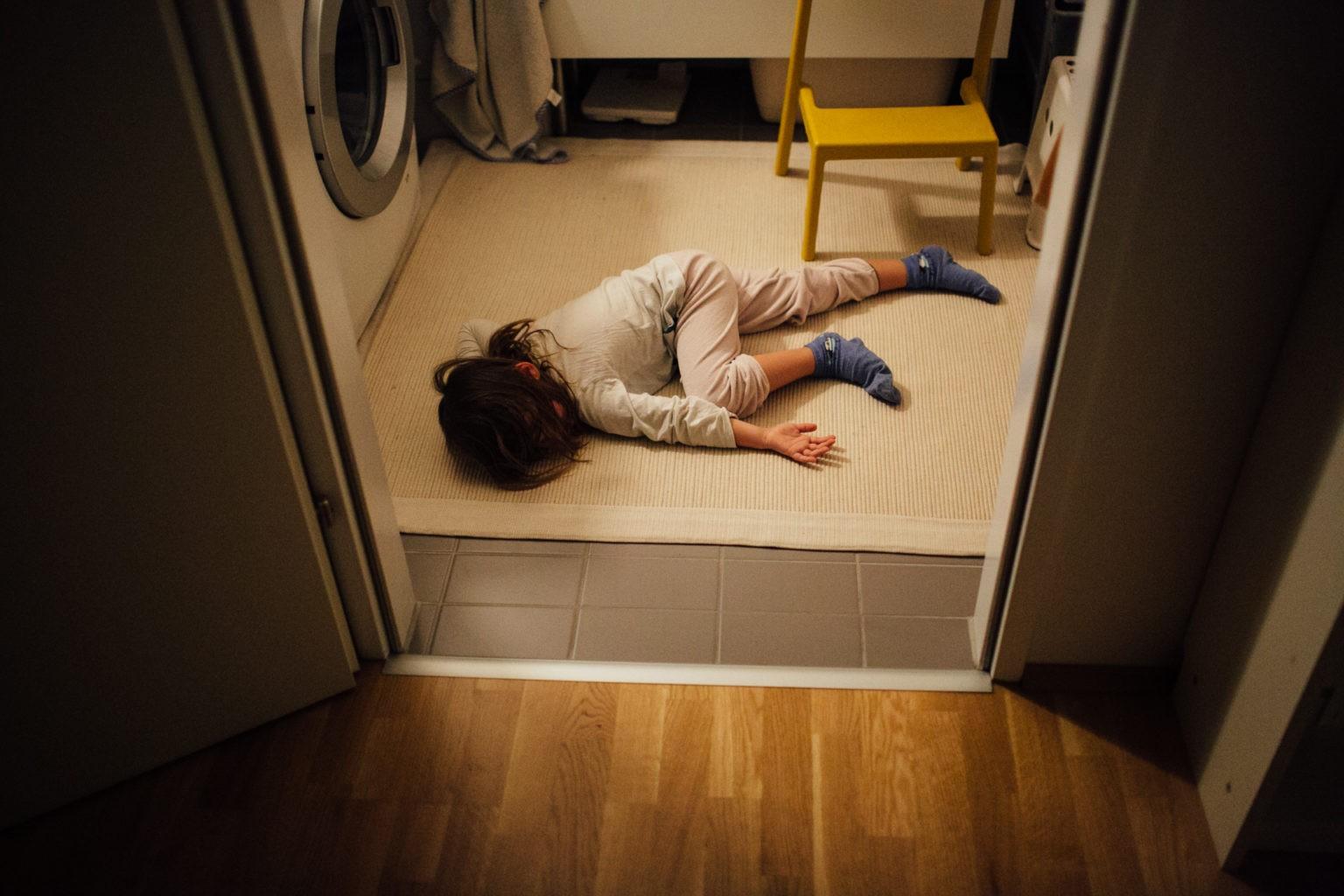 Kind liegt im Bad am Boden