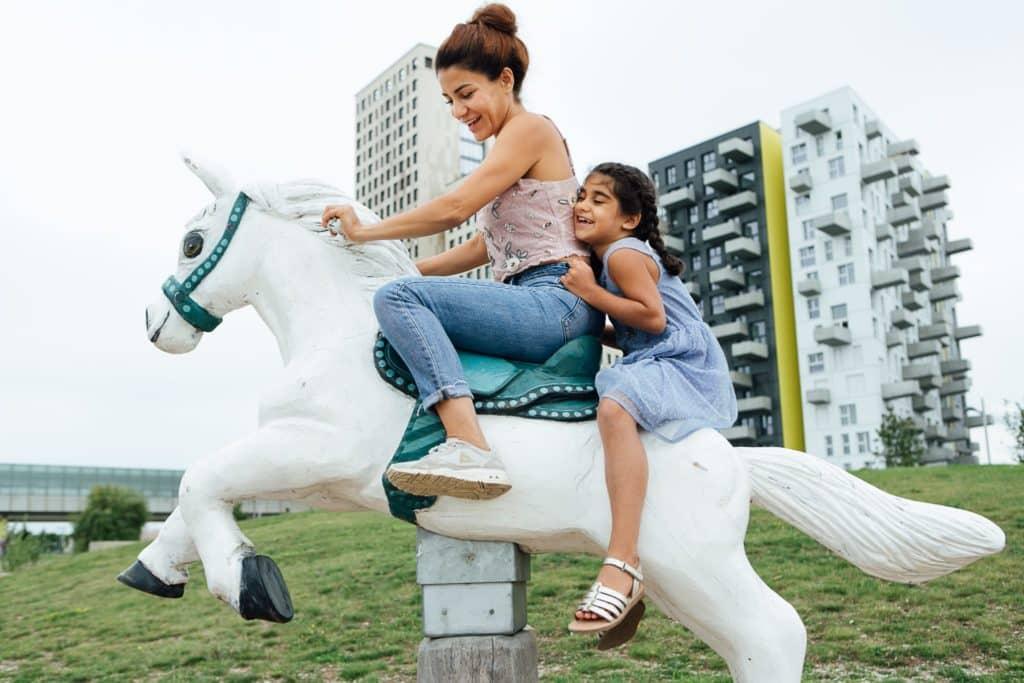 Mutter und Tochter auf einem Holzpferd